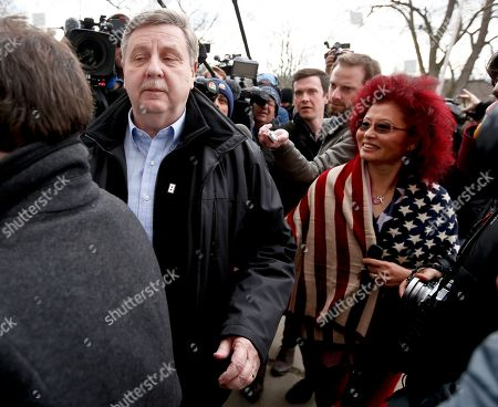 Republican Rick Saccone, left, and his wife Yong Saccone walk through members of the media as they head to the polling place to cast their ballots, in McKeesport, Pa. Saccone is running against Democrat Conor Lamb in a special election being held for the PA 18th Congressional District vacated by Republican Tim Murphy
