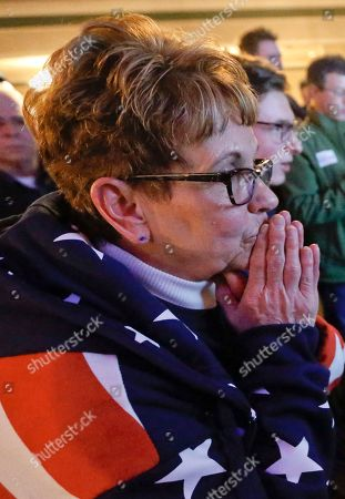 Bobbi Bauer folds her hands as he watches the results on the television that say Republican Rick Saccone was closing the gap to under 1 percent of the vote at the party watching the returns for a special election being held for the Pennsylvania 18th Congressional District vacated by Republican Tim Murphy, in McKeesport, Pa. The Pennsylvania congressional race between Democrat Conor Lamb and Saccone remains too close to call, with local elections officials still counting absentee ballots late Tuesday