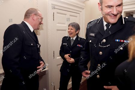 Stock Picture of Britain's Metropolitan Police Commissioner Cressida Dick (C) and Police commander Stuart Cundy (R) react as they talk with police officer of the year, PC Philip Stone, during a reception for the winners of The Met Excellence Awards at Kensington Palace