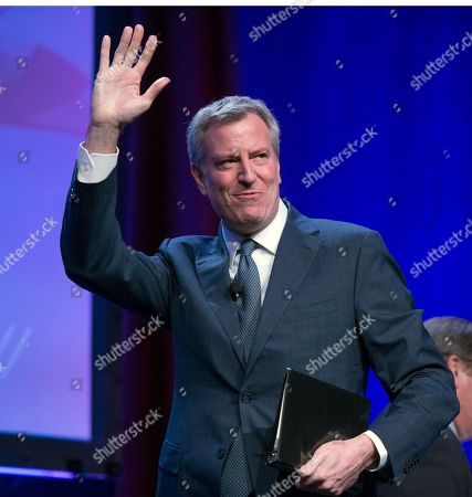 Mayor Bill de Blasio (Democrat of New York) waves to the crowd as he arrives to make remarks at the National League of Cities spring meeting at the Marriott Wardman Park Hotel in Washington, DC.