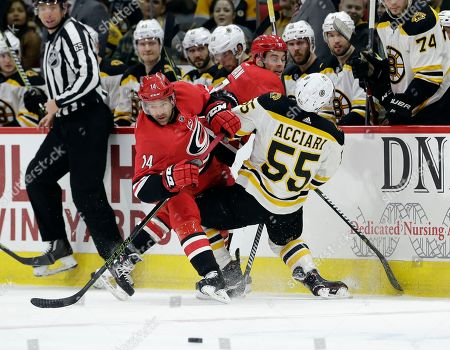 Noel Acciari, Justin Williams, Derek Ryan. Boston Bruins' Noel Acciari (55) takes a check from Carolina Hurricanes' Derek Ryan as Hurricanes' Justin Williams (14) watches the puck during the first period of an NHL hockey game in Raleigh, N.C