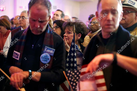 Stock Image of John Henninger, Eric Larson, Judy Kramer. John Henninger, left, and Eric Larson, right, of Cecil Township, Pa., check the time as Judy Kramer, center, of Bavington, Pa., watches late returns at the election night party for Conor Lamb, the Democratic candidate for the special election in Pennsylvania's 18th Congressional District, in Canonsburg, Pa., . The Pennsylvania congressional race between Lamb and Republican Rick Saccone remains too close to call, with local elections officials still counting absentee ballots late Tuesday