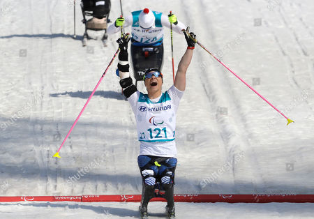 Gold medal winner Oksana Masters of the United States celebrates as she crosses the finish line to win the women's 1.1km sprint, sitting, cross-country skiing at the 2018 Winter Paralympics in Pyeongchang, South Korea