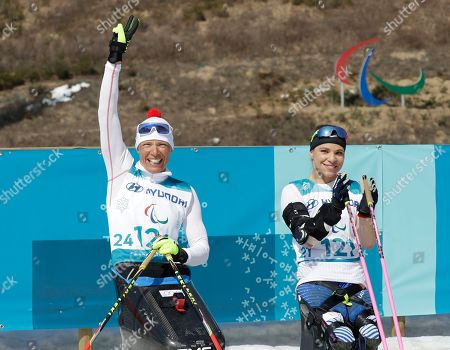 Stock Photo of Andrea Eskau, Oksana Masters. Silver medalist Andrea Eskau of Germany, left, and Gold medal winner Oksana Masters of the United States, right, celebrate after the women's 1.1km sprint, sitting, cross-country skiing at the 2018 Winter Paralympics in Pyeongchang, South Korea