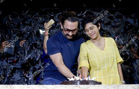 Aamir Khan, Kiran Rao. Bollywood actor Aamir Khan cuts a cake along with his wife Kiran Rao as he celebrates his birthday at his residence in Mumbai, India