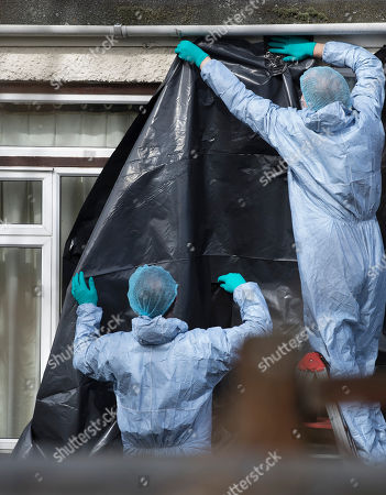 Police wearing protective clothing cover the rear windows of the house of Russian exile Nikolai Glushkov as they continue their investigation in south west London. Mr Glushkov, a friend of oligarch Boris Berezovsky, and a former deputy director of Russian state airline Aeroflot, died at his home in Monday night.