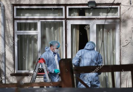 Police wearing protective clothing work at the back of the house of Russian exile Nikolai Glushkov as they continue their investigation in south west London. Mr Glushkov, a friend of oligarch Boris Berezovsky, and a former deputy director of Russian state airline Aeroflot, died at his home in Monday night.