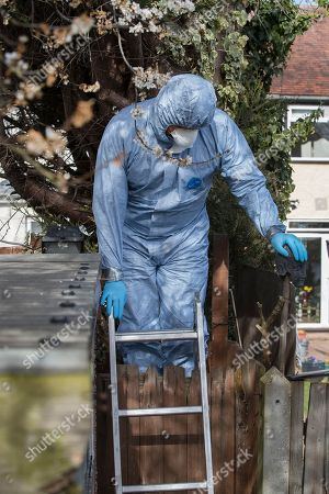 Stock Photo of Police wearing protective clothing enter the back garden of the house of Russian exile Nikolai Glushkov as they continue their investigation in south west London. Mr Glushkov, a friend of oligarch Boris Berezovsky, and a former deputy director of Russian state airline Aeroflot, died at his home in Monday night.