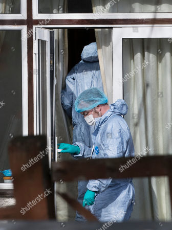 Stock Picture of Police wearing protective clothing work at the rear of the house of Russian exile Nikolai Glushkov as they continue their investigation in south west London. Mr Glushkov, a friend of oligarch Boris Berezovsky, and a former deputy director of Russian state airline Aeroflot, died at his home in Monday night.
