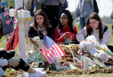 Gabrielle Benzaken, Brielle Pitteron, Falynn Kiernan. Students Gabrielle Benzaken, left, Brielle Pitterson, center, and Falynn Kiernan, right, sit at makeshift memorial for Martin Duque, one of the victims of the mass shooting at Marjory Stoneman Douglas High School, at Pine Trails Park, in Parkland, Fla. People gathered at the park as part of a nationwide protest against gun violence, following the massacre of 17 people at Marjory Stoneman Douglas High School in February