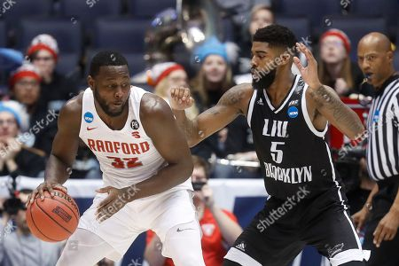 Stock Photo of Randy Phillips, Zach Coleman. Radford's Randy Phillips (32) dribbles against LIU Brooklyn's Zach Coleman (5) during the first half of a First Four game of the NCAA men's college basketball tournament, in Dayton, Ohio