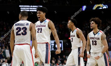 Gonzaga's Zach Norvell Jr. (23), Rui Hachimura (21), Johnathan Williams (3) and Josh Perkins (13) celebrate after Norvell Jr. made a three-point shot in the final minute of the second half of an NCAA college basketball tournament first-round game against UNC-Greensboro, in Boise, Idaho. Gonzaga won 68-64