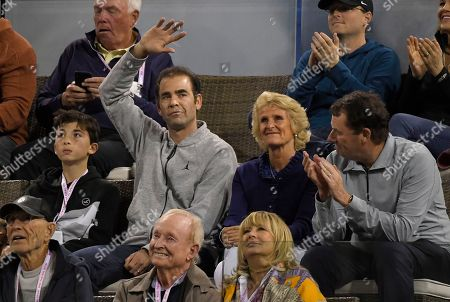 Former tennis player Pete Sampras, second from left, waves during a quarterfinal between Roger Federer, of Switzerland, and Chung Hyeon, of South Korea, at the BNP Paribas Open tennis tournament, in Indian Wells, Calif