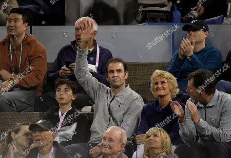 Former tennis player Pete Sampras, center, waves during a quarterfinal between Roger Federer, of Switzerland, and Chung Hyeon, of South Korea, at the BNP Paribas Open tennis tournament, in Indian Wells, Calif