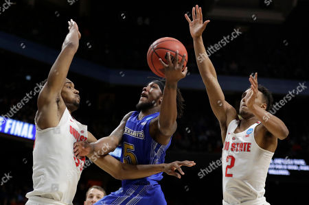South Dakota State guard David Jenkins Jr. (5) puts up a shot as Ohio State forward Keita Bates-Diop, left, and guard Musa Jallow, right, defend during the first half of a first-round game in the NCAA college basketball tournament, in Boise, Idaho