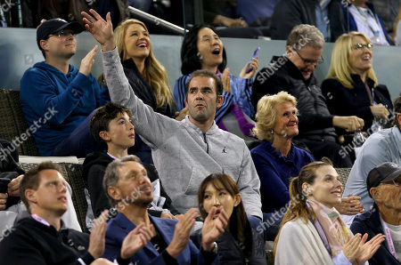 Pete Sampras acknowledges the crowd next to his son