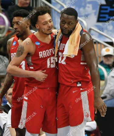 Devonnte Holland, Randy Phillips. Radford's Devonnte Holland (15) and Randy Phillips (32) console each other after the team's 87-61 loss to Villanova in an NCAA men's college basketball tournament first-round game, in Pittsburgh