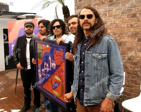 """Members of the Mexican rock band Enjambre unveil their golden disc for their album """"Imperfecto Extraño"""" in Mexico City on . From left to right are Julian Navejas, Rafael Navejas, Javier Mejia, Luis Navejas and Angel Sanchez. Enjambre is one of the headliners of the Vive Latino Festival 2018"""