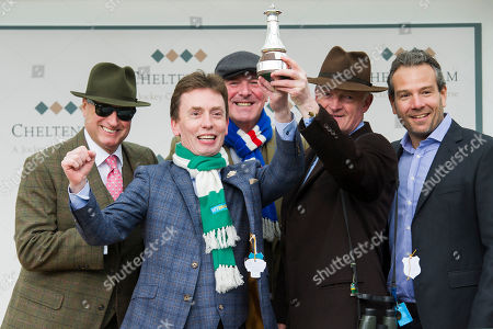 Ken Doherty representing Ireland celebrates with The BetBright Prestbury Cup as Ireland beat Great Britain, represented by Phil Tufnell, to the most wins in The Festival with Willie Mullins
