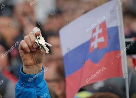 Stock Image of A man holds up keys as people celebrate the resignation of Prime Minister Robert Fico and his government as a way out of the political crisis triggered by the slayings of an investigative journalist and his fiancee, during a rally in Bratislava, Slovakia