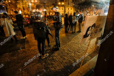 Stock Photo of A banner showing slain investigative journalist Jan Kuciak and his fiancee Martina Kusnirova, is placed against a window following a celebration rally for the resignation of Prime Minister Robert Fico and his government as a way out of the political crisis triggered by the slaying of the couple, in Bratislava, Slovakia