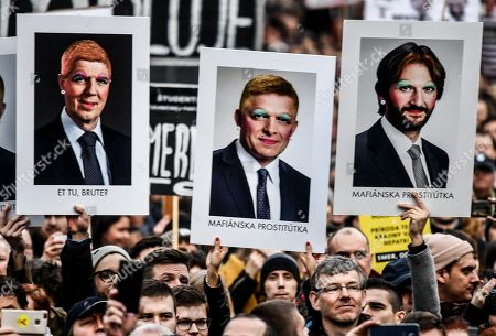 Stock Picture of People hold banners of re-painted portraits of Slovakia's Prime Minister Robert Fico (C) and Interior Minister Robert Kalinak (R) as they participate in a rally called 'Let's stand for decency in Slovakia' in Bratislava, Slovakia, 16 March 2018. Mass street protests in SLovakia started after the murder of journalist Jan Kuciak and his fiance Martina Kusnirova. Protesters are asking for an independent investigation into the murders and new, trustworthy government that will not include people suspected of corruption