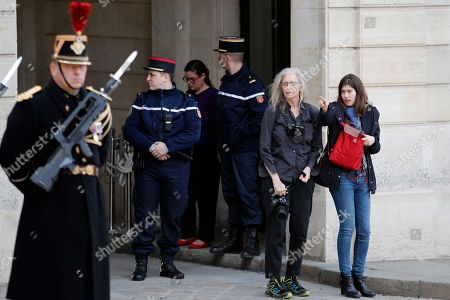 US photographer Annie Leibovitz, second right, flanked with Elysee Palace press officer Selen Daver, right, arrive to photograph French President Emmanuel Macron and Chancellor Angela Merkel during their meeting at the Elysee Palace in Paris, . German Chancellor Angela Merkel is heading to France to meet President Emmanuel Macron in her first trip abroad since her new government was sworn in