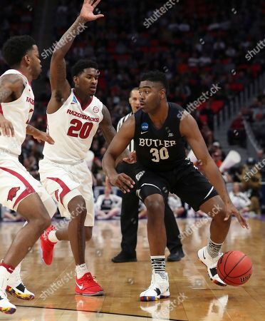 Darious Hall, Kelan Martin. Butler forward Kelan Martin (30) is defended by Arkansas forward Darious Hall (20) during the first half of a first round game in the NCAA college basketball tournament, in Detroit