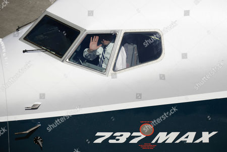 Capt. Jim Webb waves to spectators after landing a Boeing 737 MAX 7 at Boeing Field following the airplane's first flight, in Seattle