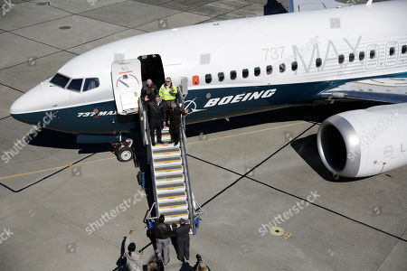 Capt. Jim Webb, first left, and Capt. Keith Otsuka, first right, are greeted after landing a Boeing 737 MAX 7 at Boeing Field following the airplane's first flight, in Seattle