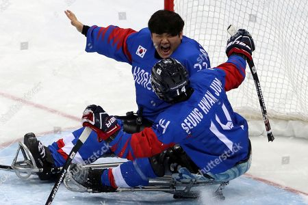 South Korea's goalkeeper Lee Jae-woong, top celebrate with teammate Jung Seung-hwan after they won against Italy in the bronze medal Ice Hockey match of the 2018 Winter Paralympics at the Gangneung Hockey Center in Gangneung, South Korea