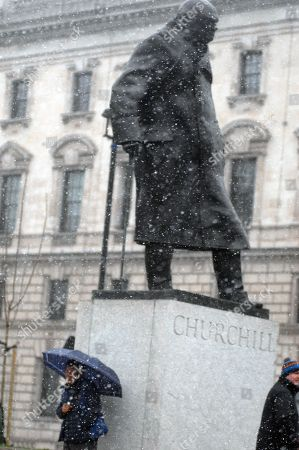 An Asian tourist in Westminster's Parliament Square in front of Big Ben shelter from the snow under an umbrella in front of a statue of Winston Churchill in the United Kingdom's capital, 17th March 2018. Snow and ice has hit parts of the United Kingdom as a cold snap dubbed the mini 'beast from the east' sweeps in with yellow 'be aware' warnings in place in parts of the country till Sunday and cancelled flights.