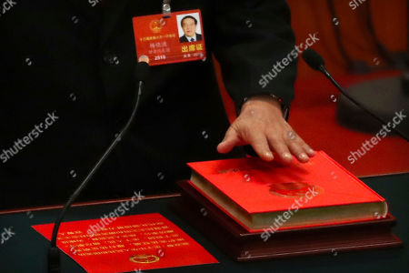 Stock Picture of Yang Xiaodu places his hand on a copy of the constitution as he takes the oath of office after being chosen as director of the National Supervisory Commission during a plenary session of China's National People's Congress (NPC) at the Great Hall of the People in Beijing, . China's ceremonial legislature appointed Premier Li Keqiang, the No. 2 leader of the ruling Communist Party, to a second five-year term Sunday and approved the appointment of a director for a new anti-corruption agency with sweeping powers