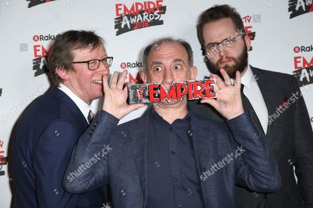 Kevin Loader, Armando Iannucci and Peter Fellows from left to right poses for photographers with the award for Best Comedy with Death of Stalin, at the Empire Film Awards in London