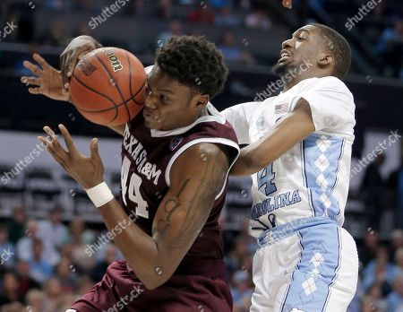 Robert Williams, Brandon Robinson. Texas A&M's Robert Williams (44) grabs a rebound in front of North Carolina's Brandon Robinson (4) during the first half of a second-round game in the NCAA men's college basketball tournament in Charlotte, N.C
