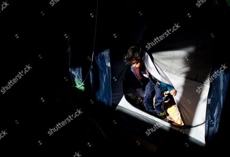Four-year-old Yandel Rivera climbs out of the tent where he is living with his family outside earthquake-damaged Independencia 18 in Mexico City. Six months after the earthquake, thousands of people remain displaced in Mexico City, many of them still awaiting news of what will happen to the properties where they once lived