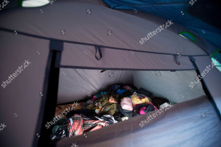 7-year-old Kaled Haebran Rivera watches videos on a cell phone inside the tent where he lives with his family outside earthquake-damaged Independencia 18 in Mexico City. Recently a donor contributed a half dozen larger weather-proof tents which have improved conditions for some of the families living in the camp