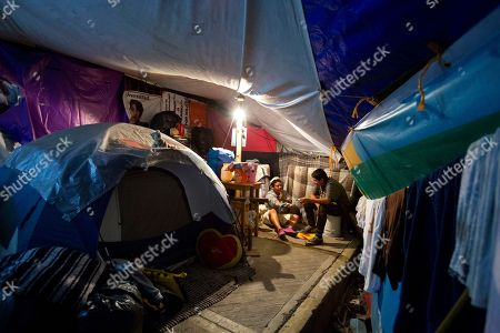 18-year-old Axel Lopez Martinez helps 13-year-old neighbor Juan Alfredo Cuaclayo Rodriguez with his homework inside one of the tent camps where residents of earthquake-damaged Independencia 18 have been living, in Mexico City. Rodriguez lives here with his mother Maria Patricia Rodriguez Gonzalez and 27-year old sister