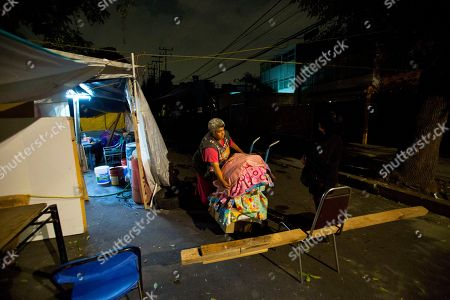 """Vendor Maria Patricia Rodriguez Gonzalez packs up her wares to bring them in for the night, at the tent camp where she has been living with her family for the last six months, outside her earthquake-damaged residence at Independencia 18 in Mexico City. Before the earthquake, Rodriguez sold dry goods, soda and candy out of a shop inside the ground-floor apartment where she had lived for 27 years. """"It makes us sad that people insult us without knowing the reality we are living,"""" Rodriguez said. """"We're not here because we want to be. We're here out of necessity"""