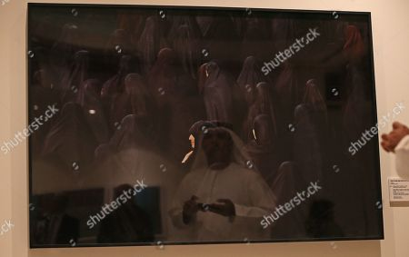 A visitor is reflected in the artwork 'Untitled' by Iranian artist Shirin Neshat during Christie's exhibition held at Jumairah Emirates Twin Towers in Gulf Emirate of Dubai, United Arab Emirates, 19 March 2018. Christie's auction will take place on 22 and 23 March 2018, presenting Modern and Contemporort Middle Eastern Arts and important watches.