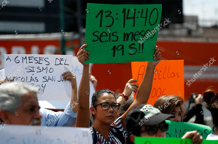 """A neighbors holds up a sign that read in Spanish """"13:14:40, six months 19S,"""" referring to the time and day of the Sept, 2017 earthquake, during a memorial ceremony on the six month anniversary of the quake, . People who lost their homes and businesses inside heavily damaged buildings have been protesting the slow rate of progress with demolitions and repairs"""
