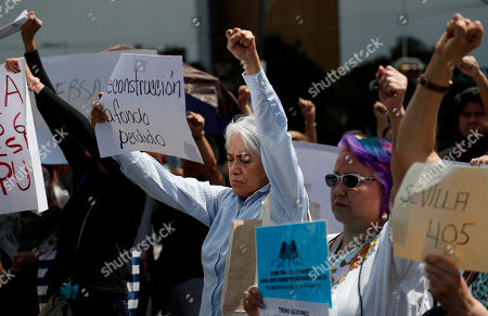 Neighbors and earthquake victims raise their fists during a memorial ceremony on the six month anniversary of the Mexico City earthquake, . People who lost their homes and businesses inside heavily damaged buildings have been protesting the slow rate of progress with demolitions and repairs