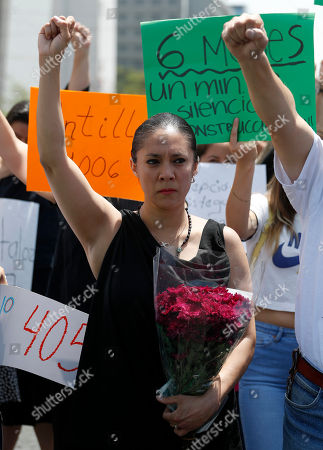 Locals raise her fists during a memorial ceremony on the six month anniversary of the Mexico City earthquake, . People who lost their homes and businesses inside heavily damaged buildings have been protesting the slow rate of progress with demolitions and repairs