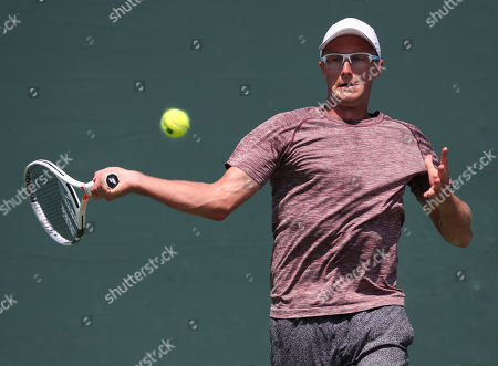 Peter Polansky from Canada plays against Reilly Opelka from the United States of America during a qualifying round at the Miami Open presented by Itau professional tennis tournament, played at the Crandon Park Tennis Center in Key Biscayne, Florida, USA