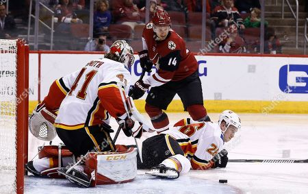 Calgary Flames defenseman Michael Stone (26) helps goaltender Mike Smith (41) block the shot of Arizona Coyotes right wing Richard Panik (14) during the second period of an NHL hockey game, in Glendale, Ariz. The Coyotes defeated the Flames 5-2