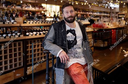 On, Russian entrepreneur Yevgeny Chichvarkin poses for a photograph in his wine shop Hedonism, in London. Amid the rising diplomatic tensions, some Russians feel they themselves trapped between stereotypes and political outrage. Chichvarkin, a one-time mobile phone entrepreneur and Kremlin critic who has lived in London for a decade, says he feels a bit less welcome. Even though he runs a an exclusive wine shop in the tony Mayfair district, plans for a new project that will create 200 jobs and contributes to art and society, his neighbors recently rejected his offer to install a trampoline in the local park