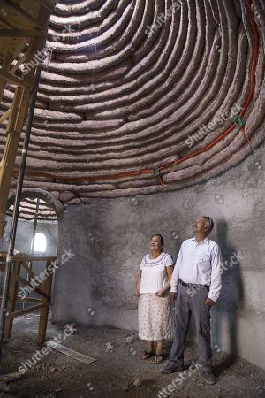 Mexican Teresa Guzman Antonio (l) and Engineer Filiberto Lara observe the house built of clay, in the city of Ixtaltepec, in the southern state of Oaxaca, Mexico, 20 March 2018.  The Mexican NGO Red Global Mx, designs and builds clay houses resistant to earthquakes of any magnitude for victims of the southern state of Oaxaca who have lost their homes due to an earthquake, said civil engineer in charge of the project, Filiberto Lara.