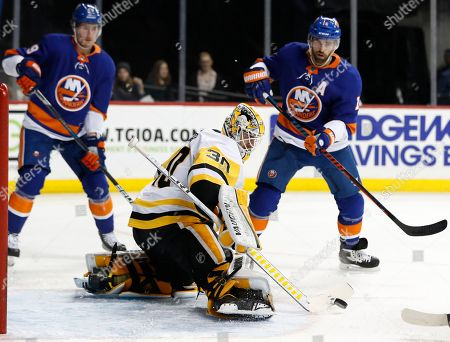 Matt Murray, Brock Nelson, Andrew Ladd. Pittsburgh Penguins goaltender Matt Murray (30) clears the crease as New York Islanders center Brock Nelson, left and Islanders left wing Andrew Ladd (16) watch during the second period of an NHL hockey game in New York