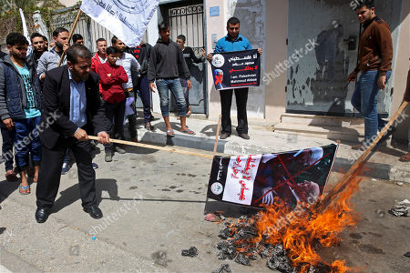 "Pro-Hamas protesters burn a picture of Palestinian President Mahmoud Abbas shaking hands with former Israeli prime minister Ehud Olmert during a demonstration against Monday's speech by Abbas that threatened more financial pressure on Gaza, in front of the Palestinian Legislative Council, in Gaza City, . Arabic reads, ""Abbas doesn't represent me, Go away Abbas"