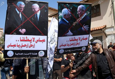 "Stock Image of Pro-Hamas protesters hold pictures of Palestinian President Mahmoud Abbas shaking hands with former Israeli prime ministers Ariel Sharon and Ehud Olmert during a demonstration against Monday's speech by Abbas that threatened more financial pressure on Gaza, in front of the Palestinian Legislative Council, in Gaza City, . Arabic reads, ""Abbas doesn't represent ua, Go away Abbas"